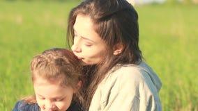 Όμορφη χαμογελώντας μητέρα που αγκαλιάζει τη χαριτωμένη κόρη της με κίτρινο φιλμ μικρού μήκους