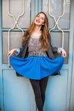 Όμορφη χαμογελώντας νέα γυναίκα που θέτει φορώντας τα περιστασιακά ενδύματα και την μπλε φούστα Στοκ Εικόνες