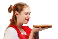 Όμορφη χαμογελώντας νοικοκυρά στην κόκκινη ποδιά με τα αστεία ponytails Στοκ φωτογραφία με δικαίωμα ελεύθερης χρήσης