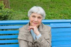Όμορφη χαριτωμένη ηλικιωμένη συνεδρίαση γυναικών στο μπλε πάγκων πάρκων Στοκ εικόνες με δικαίωμα ελεύθερης χρήσης