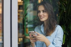 Όμορφη χαριτωμένη καυκάσια νέα γυναίκα στον καφέ, χρησιμοποιώντας το κινητό τηλέφωνο και στεμένος κοντά στο χαμόγελο παραθύρων στοκ φωτογραφία