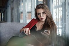 Όμορφη χαριτωμένη νέα επιχειρηματίας στον καφέ, χρησιμοποιώντας το κινητό τηλέφωνο και πίνοντας το χαμόγελο καφέ στοκ εικόνες