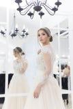 Όμορφη χαριτωμένη τρυφερή νύφη νέων κοριτσιών στο γαμήλιο φόρεμα στους καθρέφτες με την τρίχα βραδιού και την ευγενή ελαφριά σύνθ στοκ εικόνες