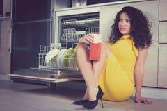 Όμορφη χαλάρωση γυναικών στη συνεδρίαση κουζινών σε ένα πάτωμα με το πακέτο του γάλακτος στοκ εικόνες