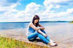 Όμορφη χαλάρωση κοριτσιών κοντά στον ποταμό Στοκ Εικόνες