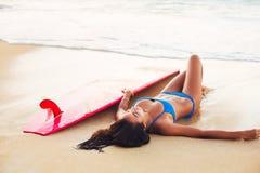 Όμορφη χαλάρωση κοριτσιών Surfer στην παραλία Στοκ φωτογραφία με δικαίωμα ελεύθερης χρήσης