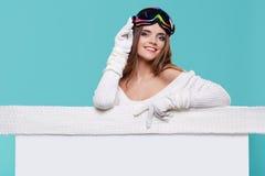 Όμορφη χειμερινή γυναίκα που κρατά έναν κενό πίνακα διαφημίσεων Στοκ Φωτογραφίες