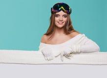 Όμορφη χειμερινή γυναίκα που κρατά έναν κενό πίνακα διαφημίσεων Στοκ φωτογραφία με δικαίωμα ελεύθερης χρήσης