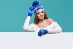 Όμορφη χειμερινή γυναίκα που κρατά έναν κενό πίνακα διαφημίσεων απομονωμένο Στοκ Εικόνα