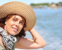 Όμορφη χρονών γυναίκα σαράντα με το καπέλο αχύρου στοκ εικόνα