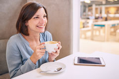 Όμορφη ώριμη γυναίκα που χαμογελά κρατώντας τον καφέ της στον πίνακα Στοκ Φωτογραφίες
