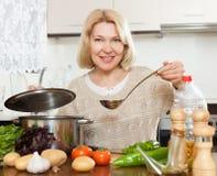 Όμορφη ώριμη μαγειρεύοντας σούπα γυναικών στοκ εικόνες