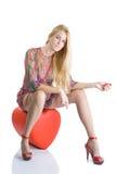 Όμορφη blondy συνεδρίαση στην κόκκινη καρδιά και τοποθέτηση Στοκ Φωτογραφίες