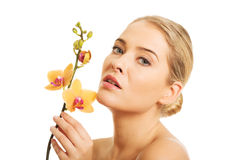 Όμορφη nude γυναίκα με το πορτοκαλί λουλούδι ορχιδεών Στοκ φωτογραφία με δικαίωμα ελεύθερης χρήσης