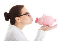 Όμορφη piggy-τράπεζα εκμετάλλευσης επιχειρησιακών γυναικών. Στοκ εικόνα με δικαίωμα ελεύθερης χρήσης