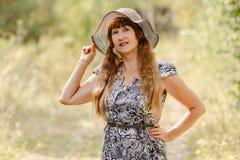 Όμορφη redhead γυναίκα πενήντα χρονών σε ένα καπέλο στα ξύλα στοκ εικόνες
