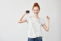 Όμορφη redhead μουσική ακούσματος κοριτσιών στο γέλιο ακουστικών Στοκ φωτογραφία με δικαίωμα ελεύθερης χρήσης