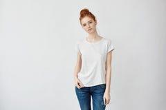 Όμορφη redhead μουσική ακούσματος κοριτσιών στο χαμόγελο ακουστικών Στοκ Εικόνα