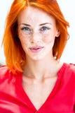 Όμορφη redhead φακιδοπρόσωπη γυναίκα που χαμογελά τα σαγηνευτικά, χείλια δαγκώματος στοκ εικόνα
