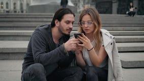 Όμορφοι άνδρας και γυναίκα που περπατούν στην οδό και που κάνουν selfie από τις έξυπνα εφαρμογές και το παιχνίδι τηλεφωνικής χρήσ απόθεμα βίντεο