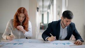 Όμορφοι επιχειρηματίες που εργάζονται μαζί με το πρόγραμμα, που κάθεται στον πίνακα στο χώρο εργασίας φιλμ μικρού μήκους