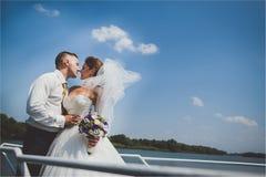 Όμορφοι μοντέρνοι νύφη και νεόνυμφος στο γιοτ πολυτέλειας που πλέει κάτω από τον ποταμό ή τη λίμνη η ημέρα γάμου τους Στοκ φωτογραφία με δικαίωμα ελεύθερης χρήσης
