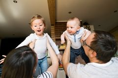 Όμορφοι νέοι γονείς που κρατούν τα χαριτωμένα μικρά παιδιά τους Στοκ Φωτογραφία