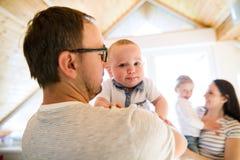 Όμορφοι νέοι γονείς που κρατούν τα χαριτωμένα μικρά παιδιά τους Στοκ φωτογραφία με δικαίωμα ελεύθερης χρήσης