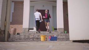 Όμορφοι νέοι γυναίκα και άνδρας που χορεύουν στο μέρος του σπιτιού που μπαίνει έπειτα στο σπίτι Στάση εξοπλισμού καθαρισμού απόθεμα βίντεο