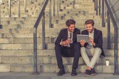 Όμορφοι νέοι επιχειρηματίες με τη συσκευή στοκ εικόνες