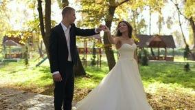 Όμορφοι νύφη και νεόνυμφος ζευγών που περπατούν στο πάρκο φθινοπώρου φιλμ μικρού μήκους