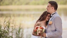 Όμορφοι νύφη και νεόνυμφος μαζί στη φύση δίπλα στη λίμνη Αγκαλιάζουν ο ένας τον άλλον, εξετάζουν τα μάτια με την τρυφερότητα φιλμ μικρού μήκους