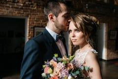 Όμορφοι νύφη και νεόνυμφος με τη γαμήλια ανθοδέσμη Στοκ Φωτογραφίες