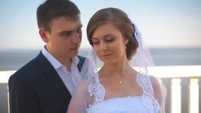 Όμορφοι νύφη και νεόνυμφος που στέκονται σε ένα μπαλκόνι που αγνοεί τη θάλασσα απόθεμα βίντεο