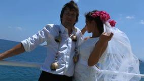 Όμορφοι νύφη και νεόνυμφος στην παραλία Νύφες πέπλων που κυματίζουν υπέροχα στον αέρα σε αργή κίνηση απόθεμα βίντεο