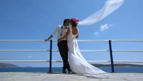 Όμορφοι νύφη και νεόνυμφος στην παραλία Νύφες πέπλων που κυματίζουν υπέροχα στον αέρα φιλμ μικρού μήκους