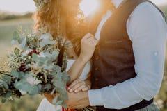 Όμορφοι νύφη και νεόνυμφος στο ηλιοβασίλεμα στην πράσινη φύση στοκ εικόνες