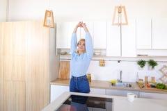 Όμορφοι περίπατοι κοριτσιών στην κουζίνα και τα τεντώματα, που απολαμβάνουν το πρωί γ Στοκ Εικόνες