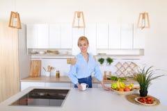 Όμορφοι περίπατοι κοριτσιών στην κουζίνα και τα τεντώματα, που απολαμβάνουν το πρωί γ Στοκ Φωτογραφία