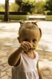 Όμορφοι περίπατοι μικρών κοριτσιών στο πάρκο κρατά ένα λουλούδι και εξετάζει τον Στοκ Εικόνες