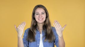 Όμορφοι προσκαλώντας πελάτες γυναικών και με τα δύο χέρια που απομονώνονται στο κίτρινο υπόβαθρο απόθεμα βίντεο