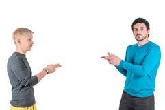 Όμορφοι τύποι που παρουσιάζουν ο ένας στον άλλο με τα δάχτυλα στοκ εικόνες
