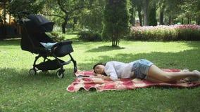 Όμορφοι ύπνοι μητέρων κοντά στη μεταφορά μωρών στο καρό στο πάρκο φιλμ μικρού μήκους