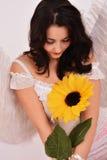 Όμορφος άγγελος κοριτσιών που κρατά έναν ηλίανθο Στοκ Εικόνες