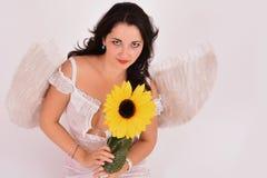 Όμορφος άγγελος κοριτσιών που κρατά έναν ηλίανθο Στοκ Φωτογραφίες