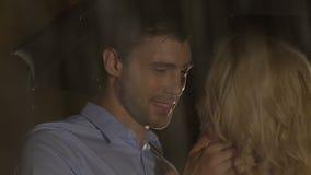 Όμορφος άνδρας που εξετάζει παθιασμένα την ξανθή γυναίκα, που χαϊδεύει ήπια, βροχερή νύχτα απόθεμα βίντεο