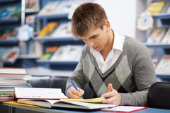 Όμορφος άνδρας σπουδαστής σε μια βιβλιοθήκη Στοκ Εικόνες