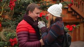 Όμορφος άνδρας και όμορφος καφές κατανάλωσης γυναικών στην αγορά Χριστουγέννων παράδοσης Η σύζυγος και ο σύζυγος εξετάζουν μεταξύ απόθεμα βίντεο