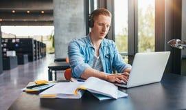 Όμορφος άνδρας σπουδαστής σε μια πανεπιστημιακή βιβλιοθήκη Στοκ Εικόνα