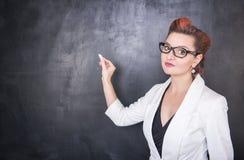 Όμορφος δάσκαλος με το κομμάτι της κιμωλίας στο υπόβαθρο πινάκων Στοκ φωτογραφία με δικαίωμα ελεύθερης χρήσης